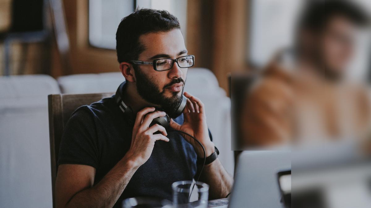 Man adjusting headphones while looking at computer screen