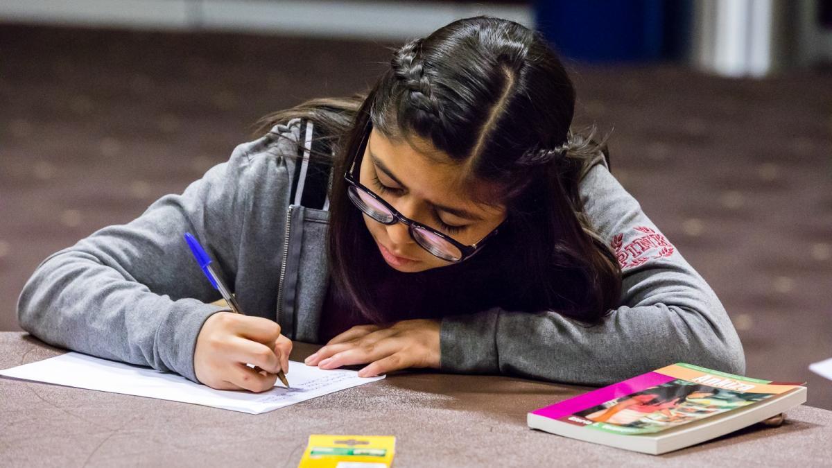 A girl writes near a book at ASU's El Dia celebration in 2018 / Photo by Bruce Matsunaga
