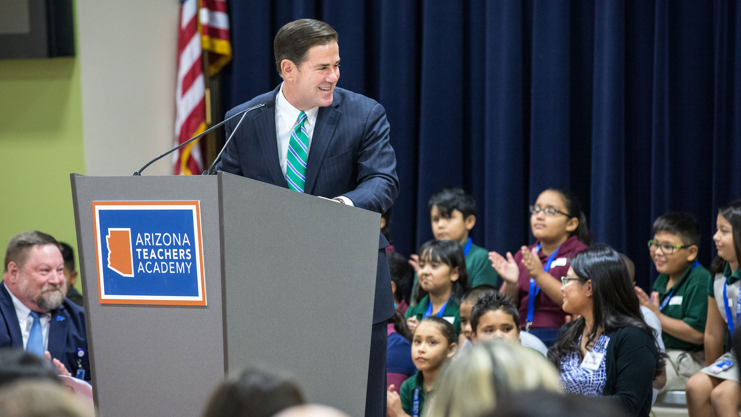 Gov. Doug Ducey speaks to elementary students onstage