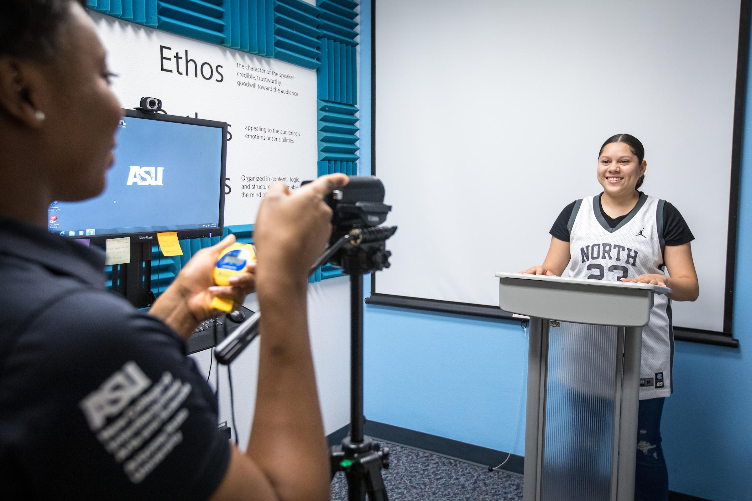 student filming woman speaking