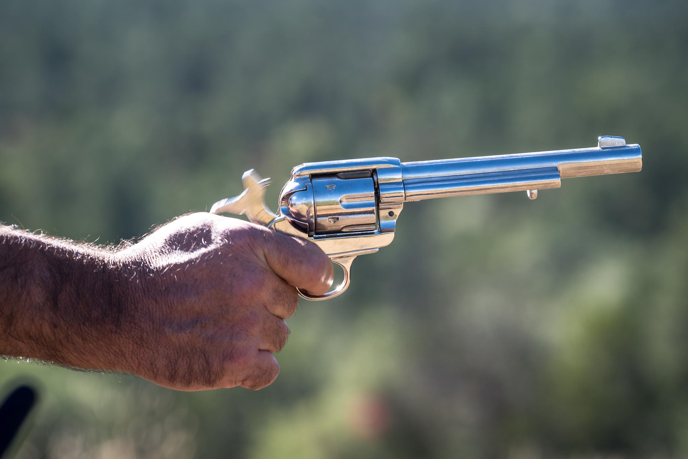 hand holding colt revolver