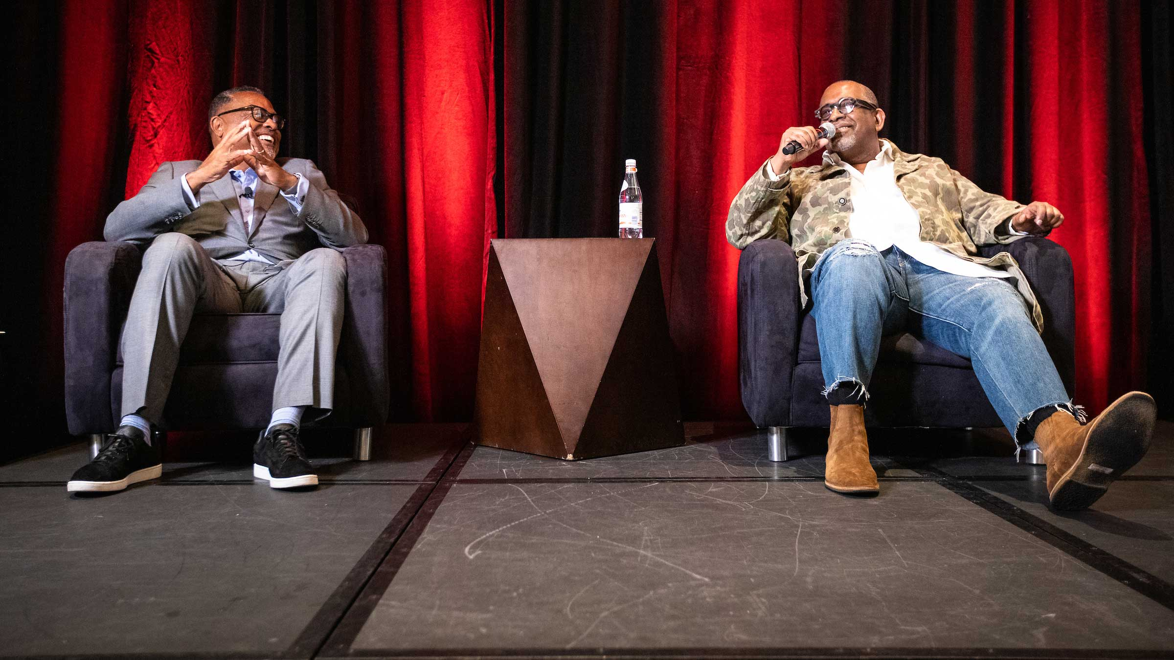 Two men sit onstage for a discussion about sports and diversity