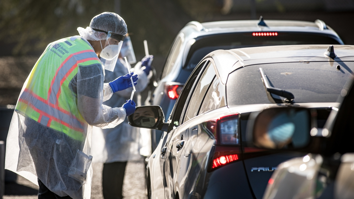 Man in protective gear reaching into a car