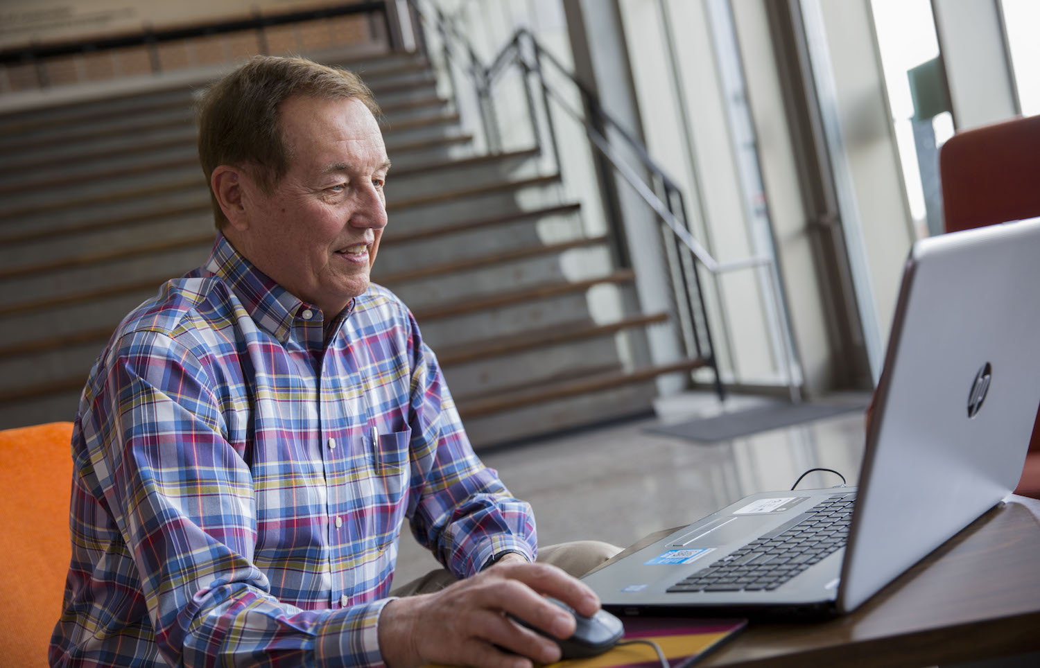 Photo of man sitting in front of a laptop.