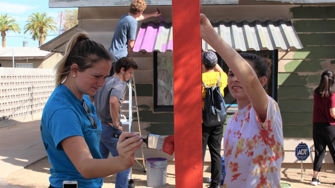 Two ASU students paint during a day of service