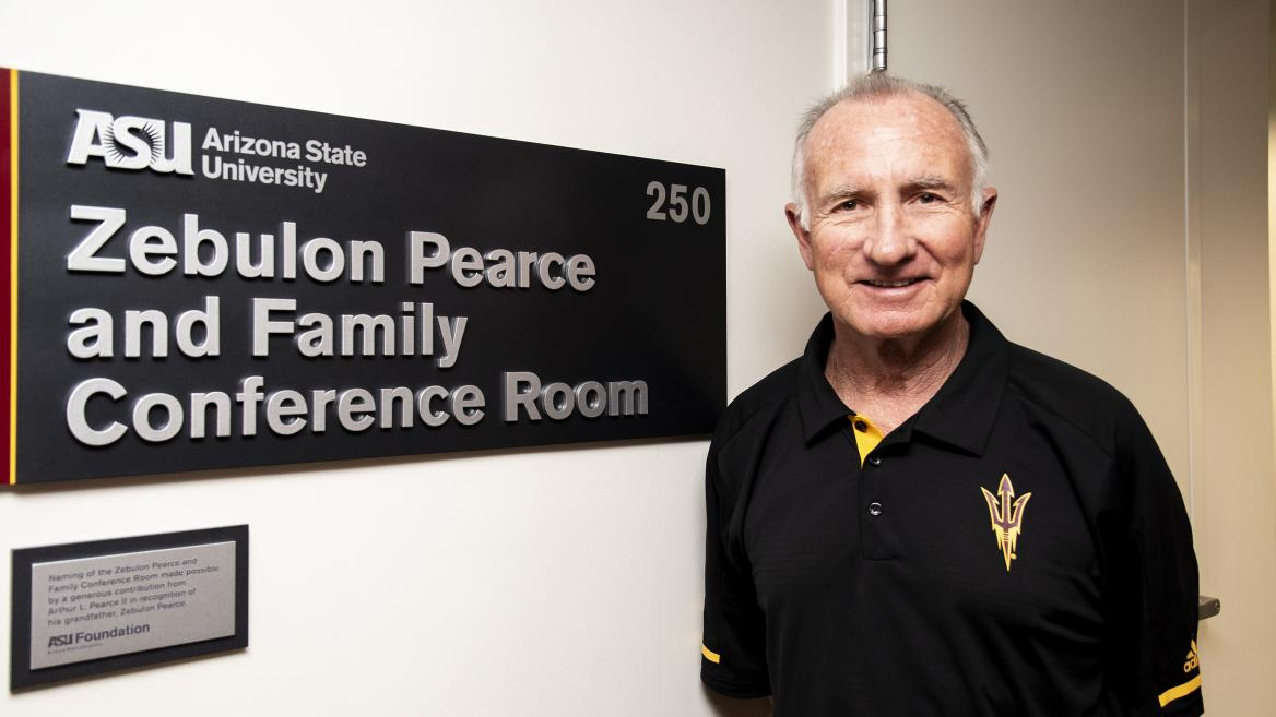 """Arthur """"Art"""" Pearce II poses in front of the newly-unveiled Zebulon Pearce and Family Conference Room at Armstrong Hall."""