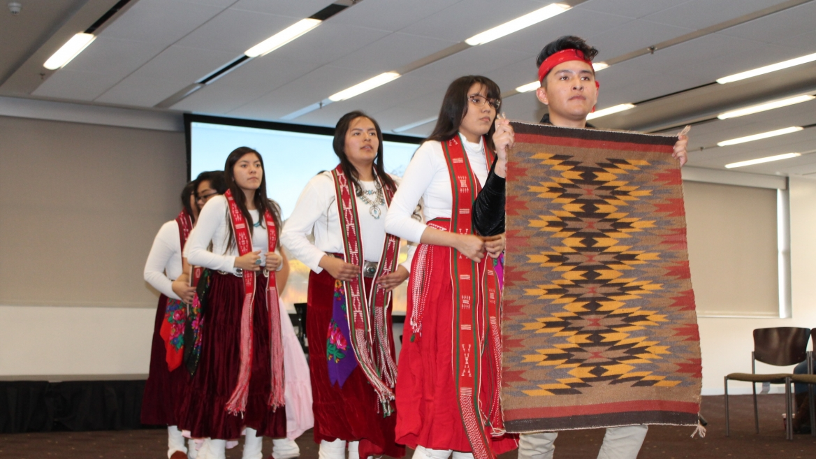 High school students wearing white and red cultural outfits participate in a Language Fair presentation. The students are standing in a line, with the front student displaying a woven rug or tapestry with a red, yellow, and black angular design.