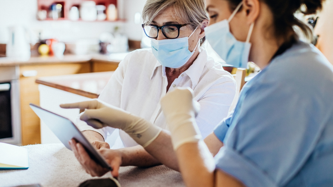 two health care workers wearing masks while looking at a tablet
