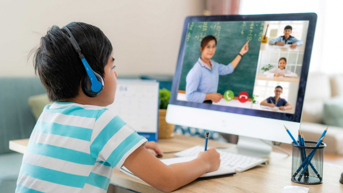 A young student watches his teacher on the laptop screen