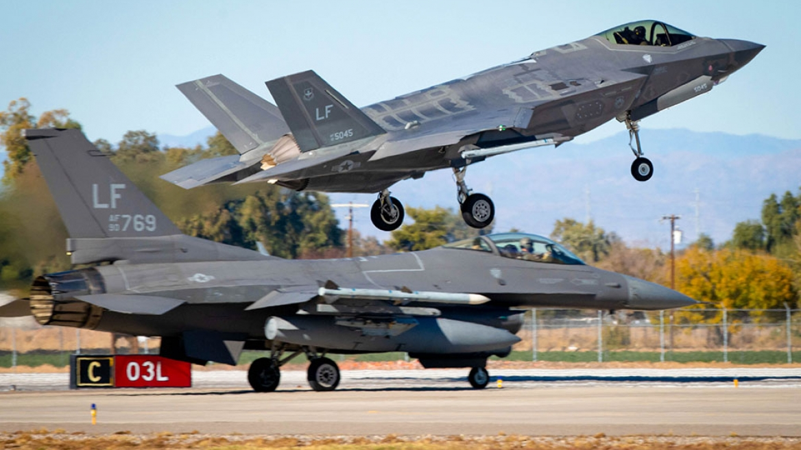 An F-35A Lightning II lands while an F-16 Fighting Falcon prepares for takeoff at Luke Air Force Base.