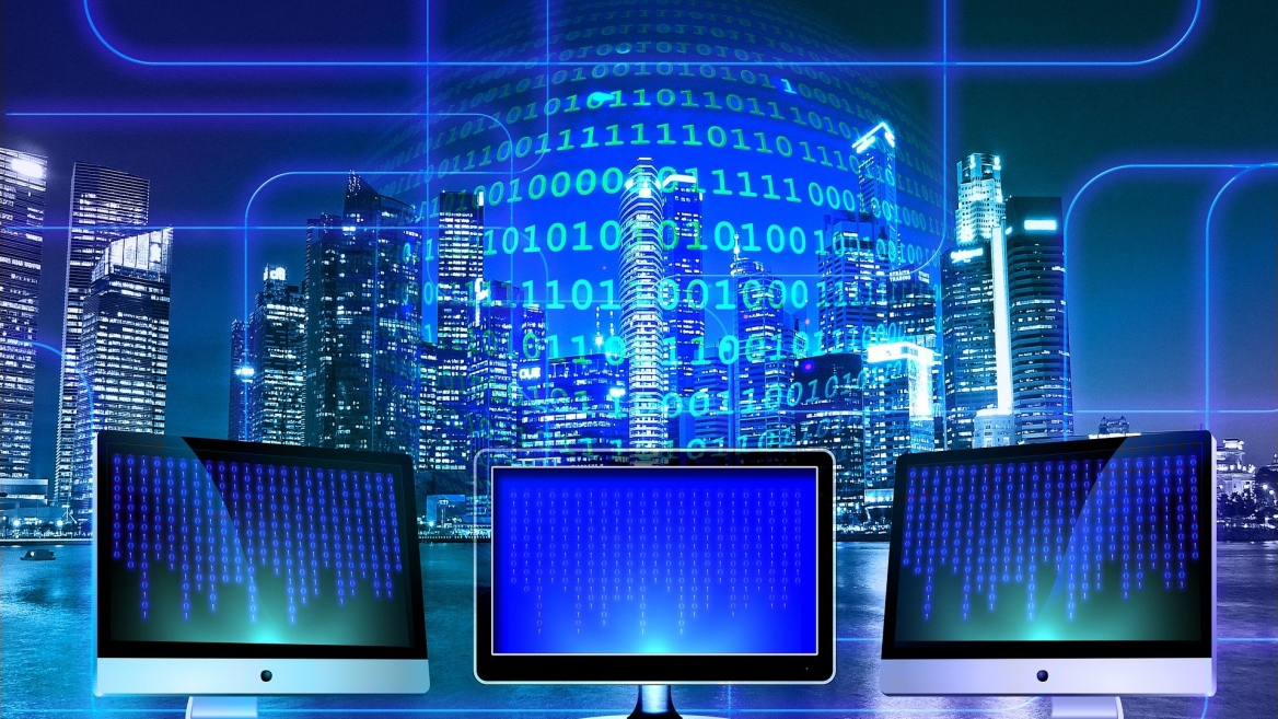 abstract image with computer screens in foreground and a city scape in the background