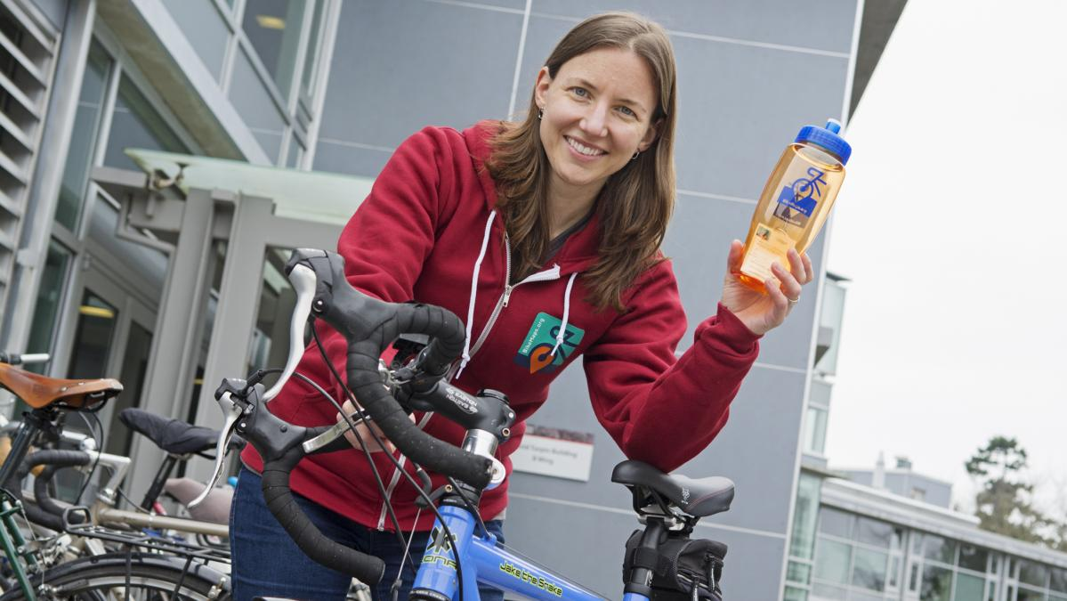 woman next to bike holding water bottle