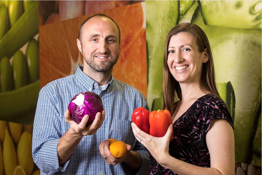 two professors holding fruit and vegetables