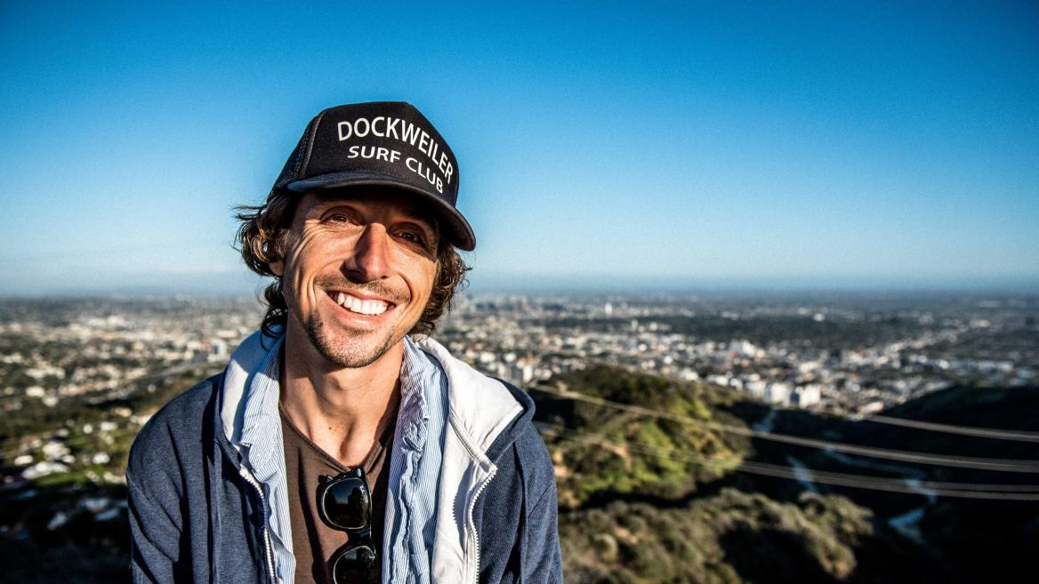"Author Nic Sheff smiles atop a mountain in a black baseball cap reading ""Dockweiler Surf Club"" and blue open jacket"