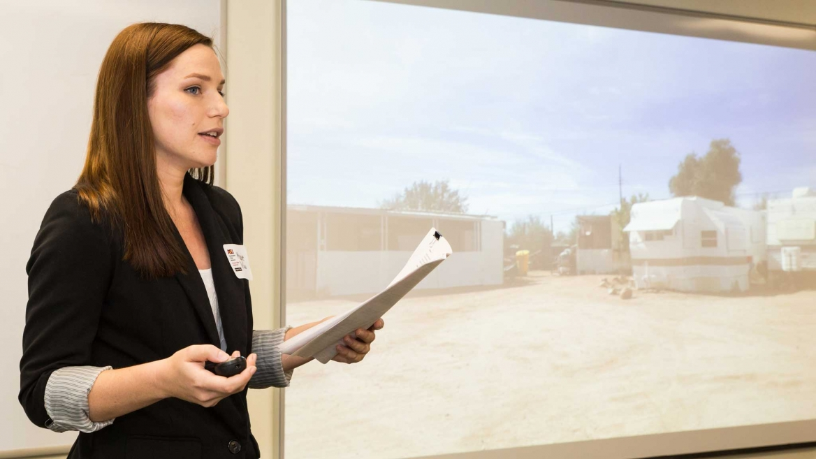 Woman in professional wear, Maggie Dellow, giving presentation with mobile home park depicted on slideshow