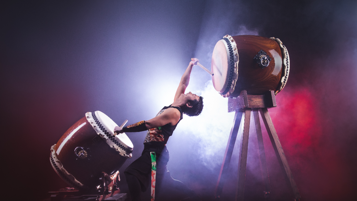 man drumming on two large drums while backlit with fog surrounding him